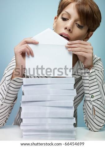 caucasian secretary closing pile of envelopes. Vertical shape, front view, waist up, copy space - stock photo