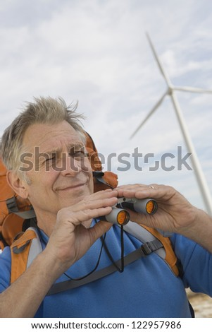 Caucasian senior male holding binoculars at wind farm - stock photo