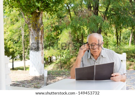 Caucasian senior man talking on mobile phone while sitting at a table and reading outdoors, with green foliage in the background - stock photo