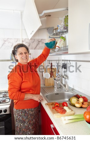 Caucasian senior woman in the kitchen with vegetables, preparing meal - stock photo