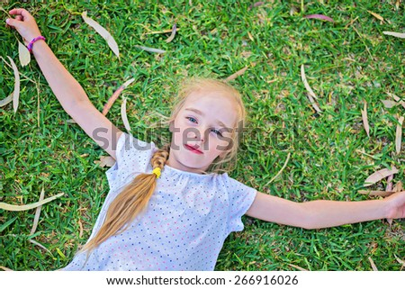 Caucasian small girl extend your arms lying on green grass, top view - stock photo