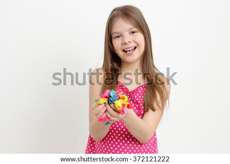 Caucasian smiley little girl holding balloons not inflated - stock photo
