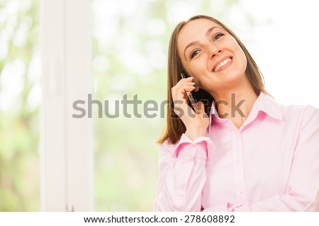 Caucasian smiling business woman is having a phone call - stock photo