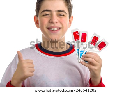 Caucasian smooth-skinned boy holds four 3D Cinema paper eyeglasses with red and sky-blue lenses with left hand while making success sign with right hand