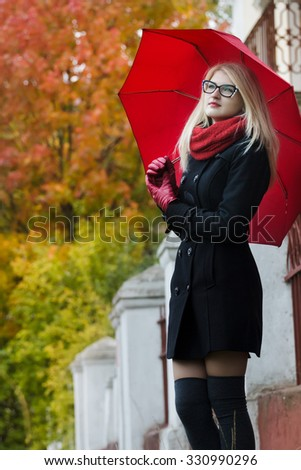 Caucasian student girl with red fully collapsible umbrella in hands and cat eye glasses is posing at autumn street background - stock photo