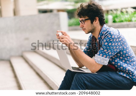Caucasian student sitting on steps and using smartphone - stock photo