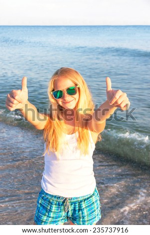 Caucasian teen girl showing thumbs up on the sea background. Happy smiling  teenager is wearing sunglasses, enjoying sea and having fun. Travel (vacation), adventure concept. Close up, outdoor. - stock photo