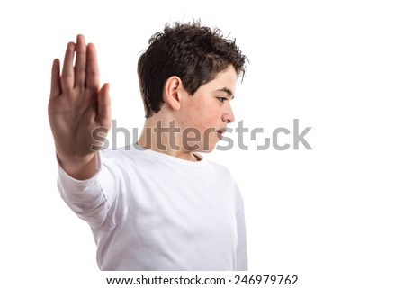 Caucasian teen with acne skin in a white long sleeve t-shirt smiles making Talk to the hand gesture with right hand - stock photo