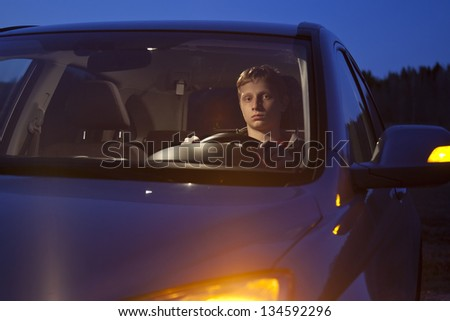 Caucasian Teenage Boy Sitting in Car at Night - stock photo