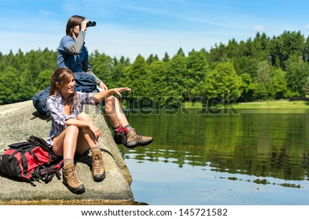 Caucasian teenage hikers birdwatching at lake - stock photo