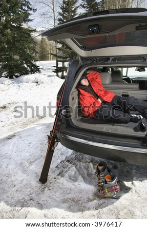Caucasian teenager sleeping in back of SUV with ski gear. - stock photo