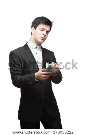 caucasian thoughtful young businessman in black suit counting money isolated on white - stock photo