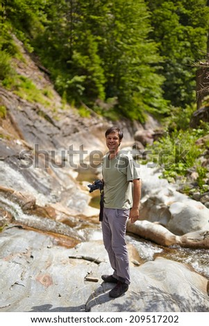 Caucasian tourist taking photos in the mountains - stock photo