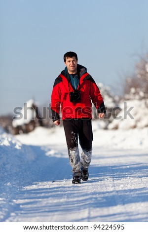 Caucasian tourist with camera in a winter day - stock photo