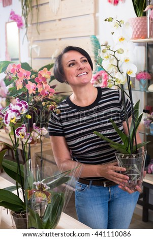 caucasian woman choosing a potted multicolored phalaenopsis flower in the floral boutique - stock photo