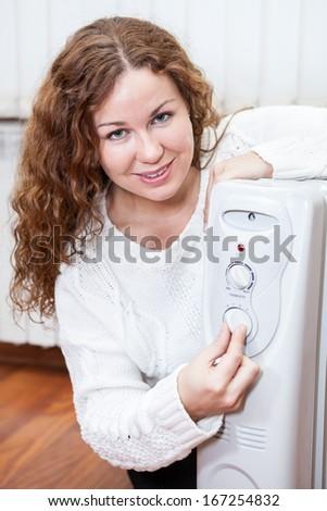 Caucasian woman controlling temperature of oil heater - stock photo