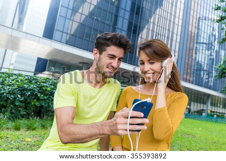 Caucasian woman enjoy the music with her boyfriend showing to her - stock photo
