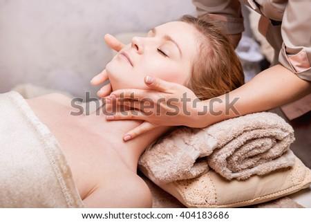Caucasian woman having anti-aging Face massage.Spa Salon rejuvenating Face  massage, closeup - stock photo