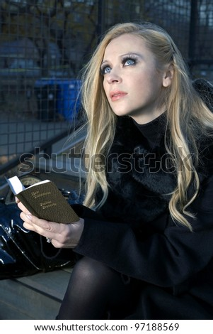 Caucasian woman holding a small Bible while outdoors.