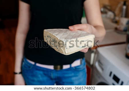 Caucasian woman holding brie cheese with the focus o nthe cheese - stock photo