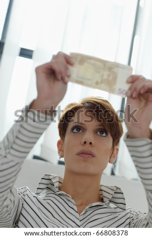 caucasian woman holding 50 euro up to the light, examining watermarks. Vertical shape, front view, copy space