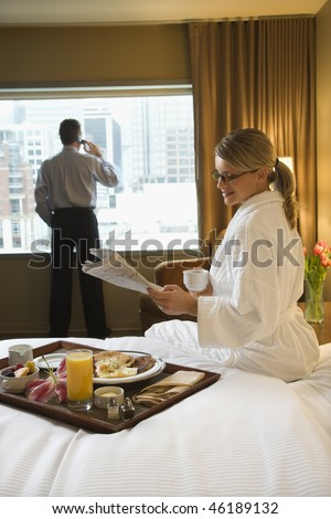 Caucasian woman in a robe sits on a hotel bed while reading the newspaper. A man stands in the background talking on his mobile phone. Vertical shot. - stock photo