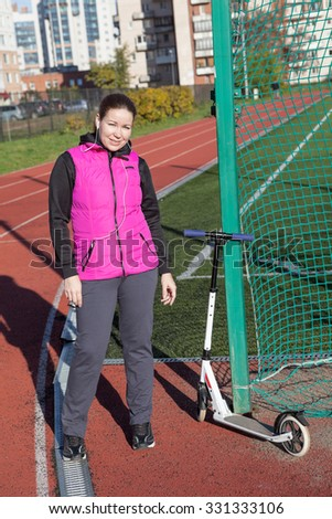 Caucasian woman in sport wear with kick scooter standing on playing field of stadium - stock photo
