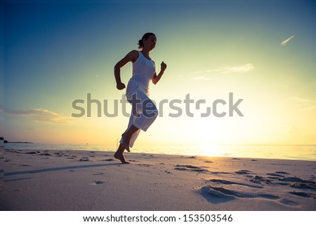 Caucasian woman jogging at seashore - stock photo
