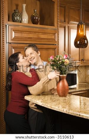 Caucasian woman kissing Caucasian man on cheek as he arranges flowers in vase in kitchen. - stock photo