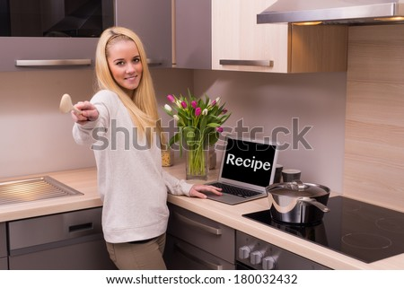 Caucasian woman looking for a recipe on the laptop computer.