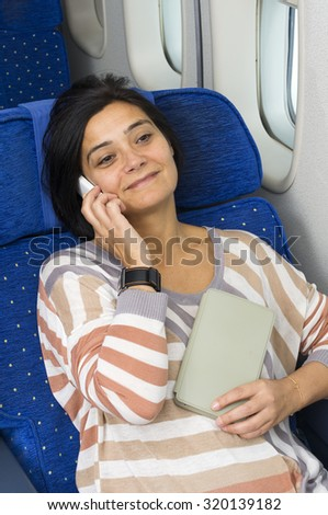 caucasian woman passenger in airplane using mobile and  tablet smart devices  in comfortable flight and trip - stock photo