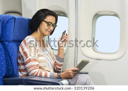 caucasian woman passenger in airplane using mobile and  tablet smart devices with headphones