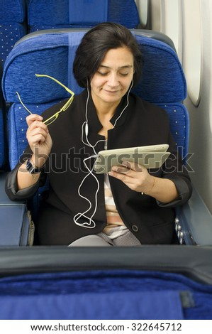 caucasian woman passenger in airplane using  tablet smart device with headphones  in comfortable flight and trip  - stock photo