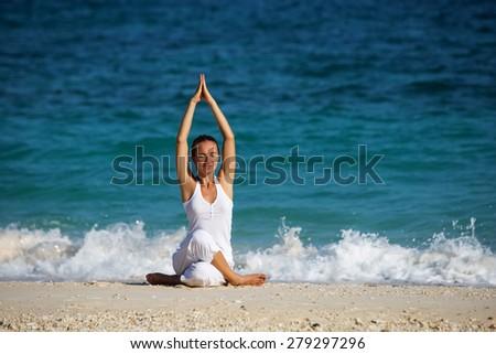 Caucasian woman practicing yoga at seashore - stock photo