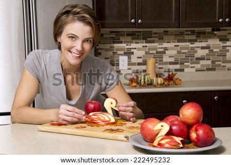 caucasian woman preparing apple thanksigiving decorations in the kitchen - stock photo