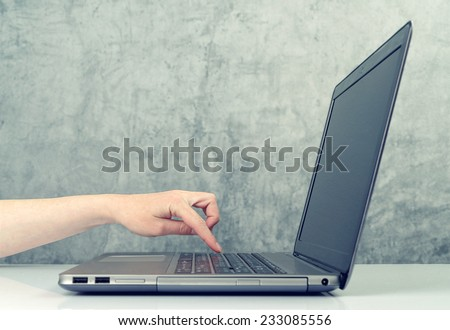 Caucasian Woman pressing the button on laptop computer keyboard. Blue toned image. - stock photo