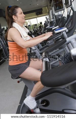 Caucasian woman riding an exercise bike - stock photo