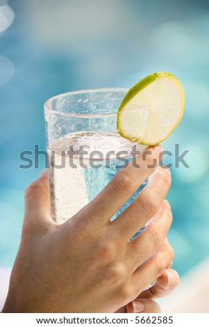 Caucasian woman's hands holding drink glass garnished with lime slice next to pool.