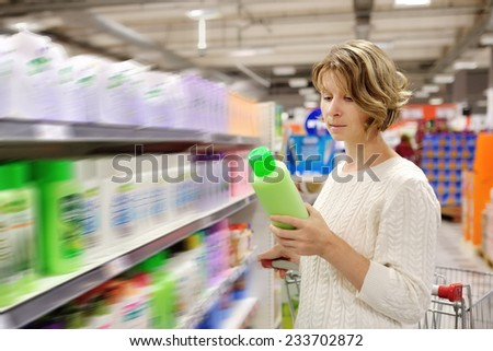 caucasian woman shopping and choosing goods at the supermarket
