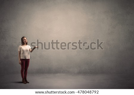 Caucasian woman standing in front of a blank grunge wall