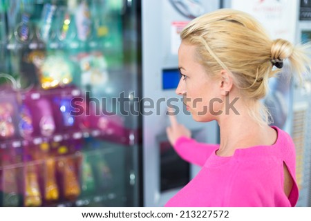 Caucasian woman wearing pink using a modern vending machine. Her right hand is placed on the key pad. - stock photo