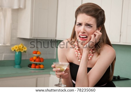 Caucasian woman with a martini in her kitchen sobs - stock photo