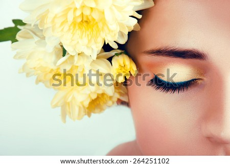 Caucasian woman with bright yellow makeup and chrysanthemum wreath around her head - stock photo