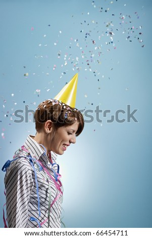 caucasian woman with confetti and streamers on shirt. Vertical shape, side view, waist up, copy space