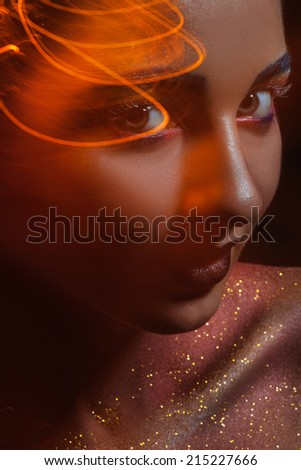 Caucasian woman with creative orange light looking at camera in studio - stock photo
