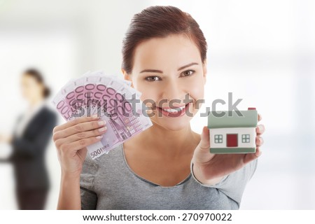 Caucasian woman with euros and house. - stock photo