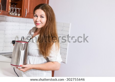 Caucasian woman with steel electric tea kettle in hands, copy space at back