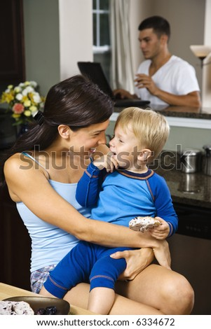 Caucasian woman with toddler son in kitchen with father on laptop in background. - stock photo