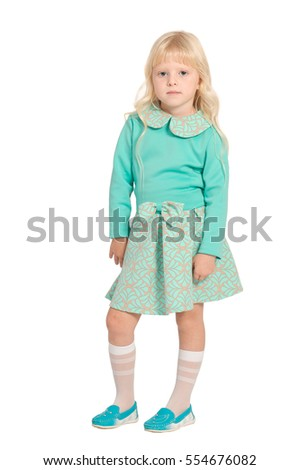Caucasian young blond girl in light green dress standing isolated on white