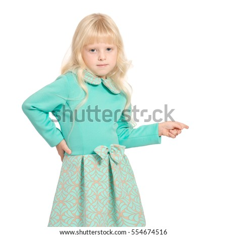 Caucasian young blondy girl in light green dress standing isolated on white pointing to the right with finger